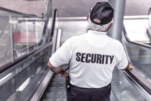 A picture of a security guard going down an escalator