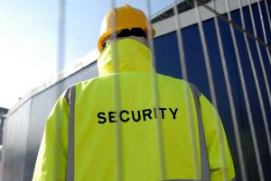 An image of a security guard from Umbrella Security Services, wearing a high visibility jacket and a hard hat, facing away from the camera.
