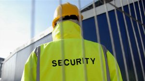 "An image of a security guard in a high visibility jacket with the word ""Security"" on the back and a yellow hard hat."