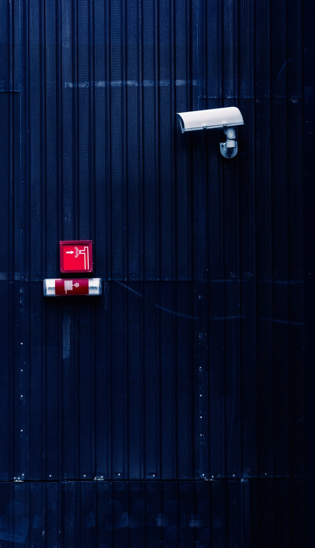 An image of a security camera provided by Umbrella security Services, mounted on a wall.