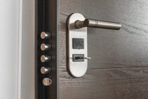 An image of a key inside a door with multiple locks.